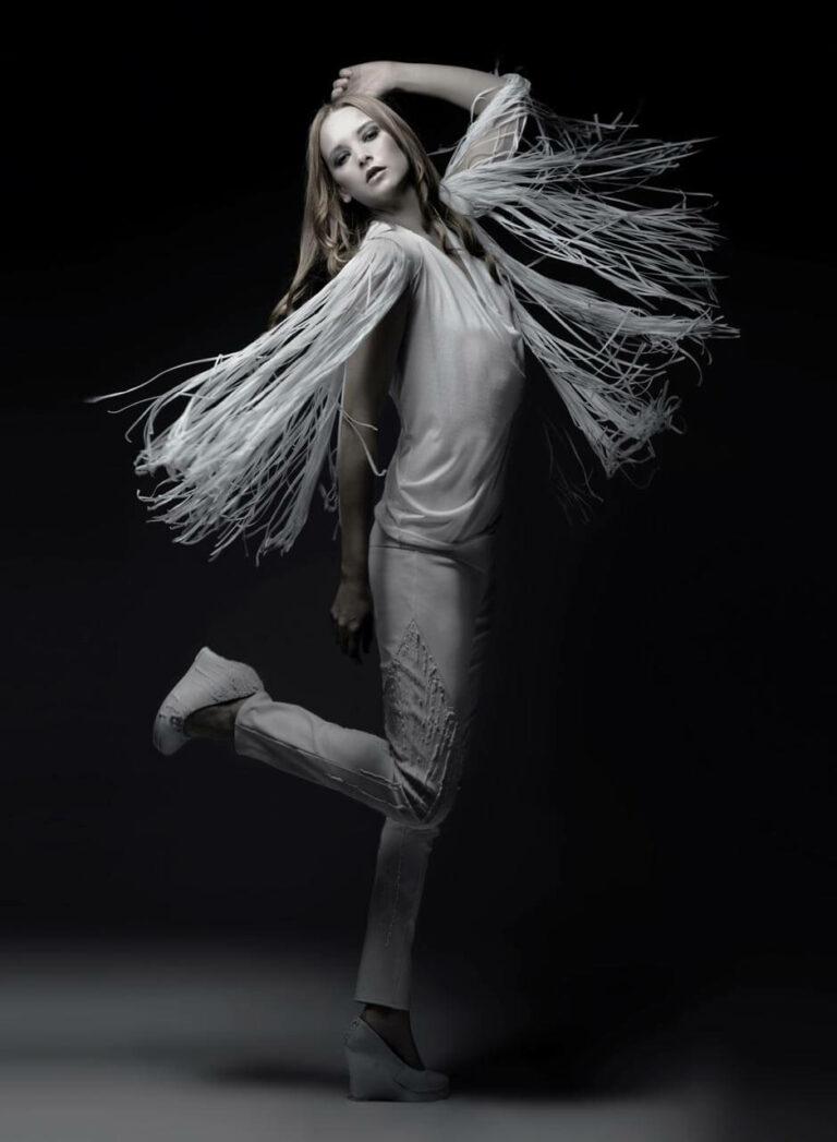 Weißes, schulterfreies Oberteil mit Fransen, weiße Jerseyhose mit Silikonapplikation, weiße Lederschuhe mit Keilabsatz und Silikonapplikation. SHAROKINA Polymorph
