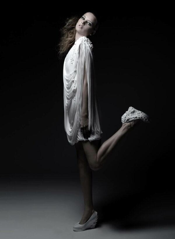 Weißes Chiffonkleid, einseitig schulterfrei, mit Applikation und Fransen, weiße Lederschuhe mit dreidimensionalen Applikationen. SHAROKINA Polymorph