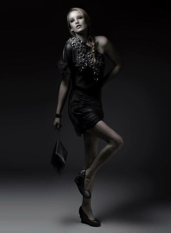 Transparentes, schwarzes Chiffontop mit Metallicapplication, geraffter schwarzer Chiffonrock, Ledertasche in Kristallform, Schuhe mit Keilabsatz aus Metallicleder mit Applikation. SHAROKINA Polymorph